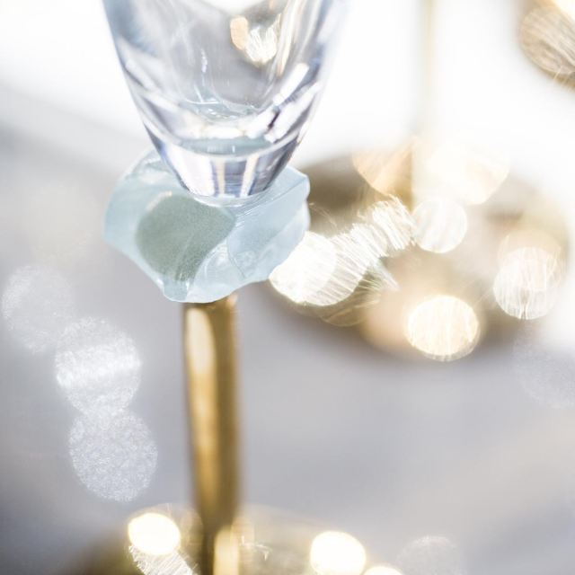 Glass champagne flute Amar by the tableware designer Anna with a brass stem and glass gem.