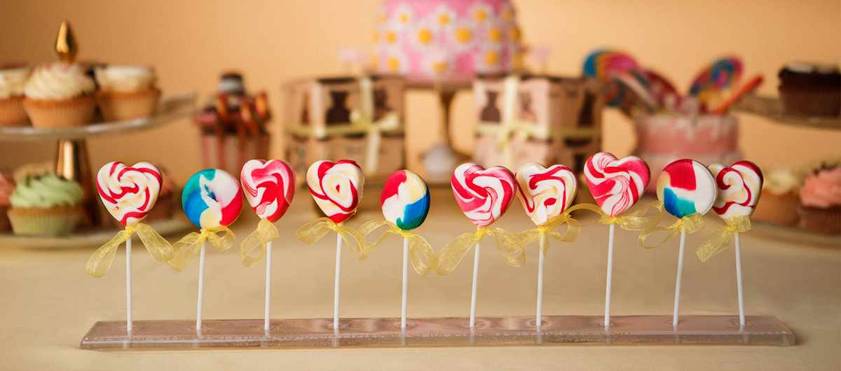 Baby Shower Candy buffet with an elegant lollipop stand by Anna Vasily with colourful heart shaped lollipops.