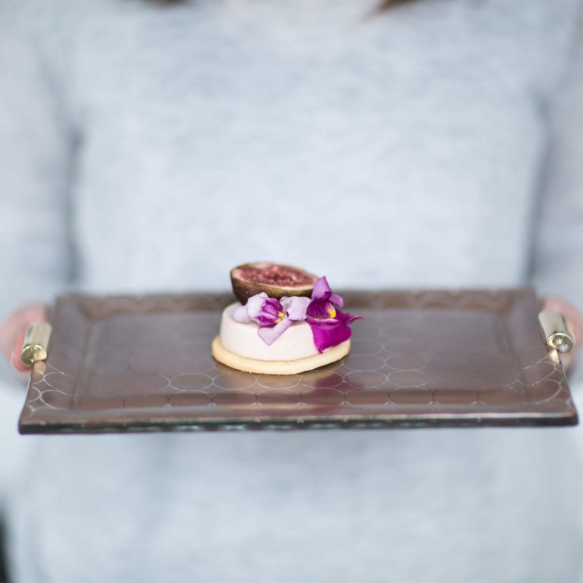 Woman in grey shirt holding a handcrafted brown charger plate by a tableware designer with brass handles and a small dessert on top