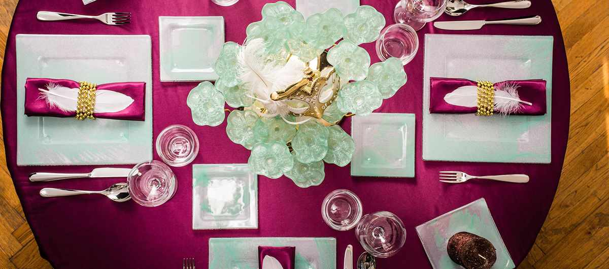 Top view of a festive purple table with mint green dinnerware and a centerpiece decorated with a carnival mask for Mardi Gras by AnnaVasily