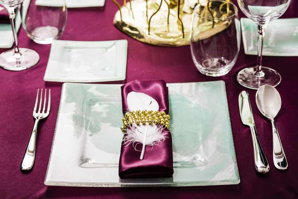 Festive table dinner set with a mint green square charger plate and a purple napkin in a napkin ring with a feather