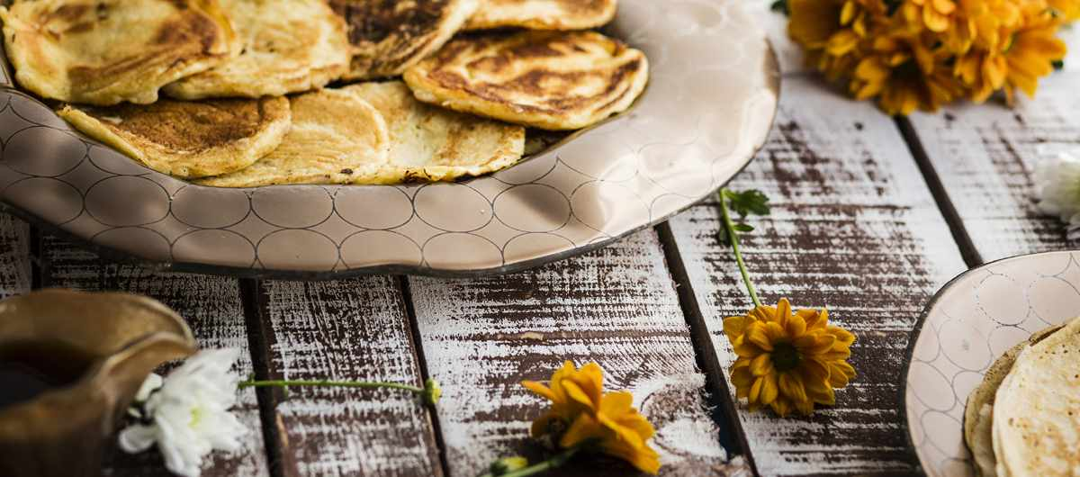 Brown Irregular Platter Tama by AnnaVasily with lots o small pancakes on a wooden table with autumn leaves