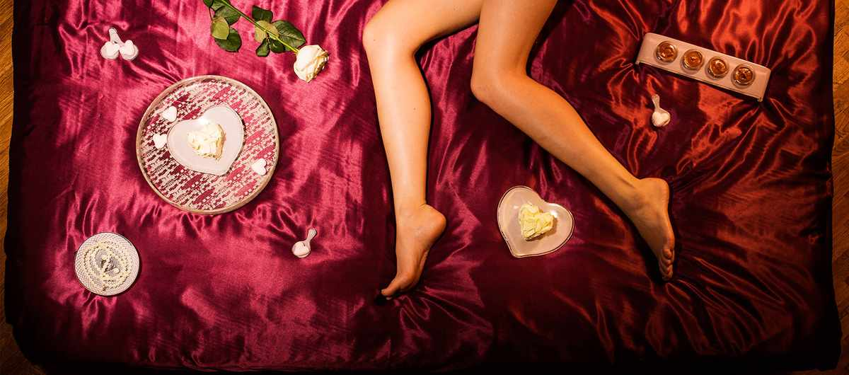 Red satin sheets with pink Valentine's Day dinnerware with heart plates and a woman's bare legs.
