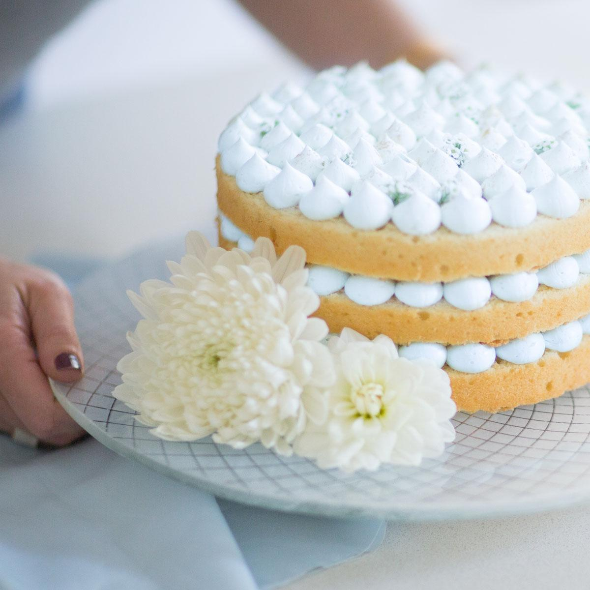 The Harmo white cake stand by the tableware desginer Anna with a naked cake with blue frosting and flowers.