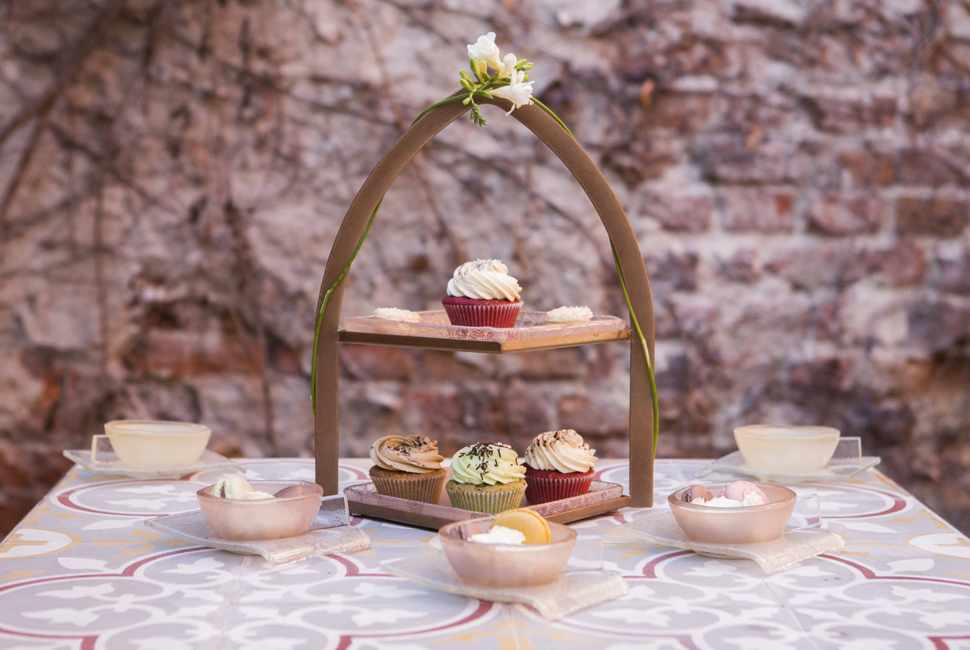 Afternoon Tea Stands - Wate by Anna Vasily - Small Pink Modern 2 Tier Stand With Patterned Square Plates on a Table With Cupcakes and Tea Cups