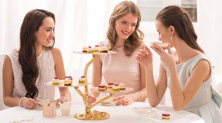3 women talking over coffee and desserts with tableware designer Anna's coffee cups and modern high tea stand.