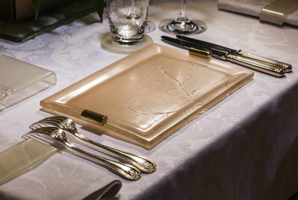 Rose gold elegant dinner plates with bronze handles on a white tablecloth with gold silverware.