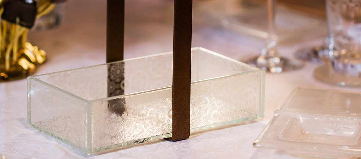 Elegant Table Decorations - A glass bread basket with a brown metal handle on an elegant table.