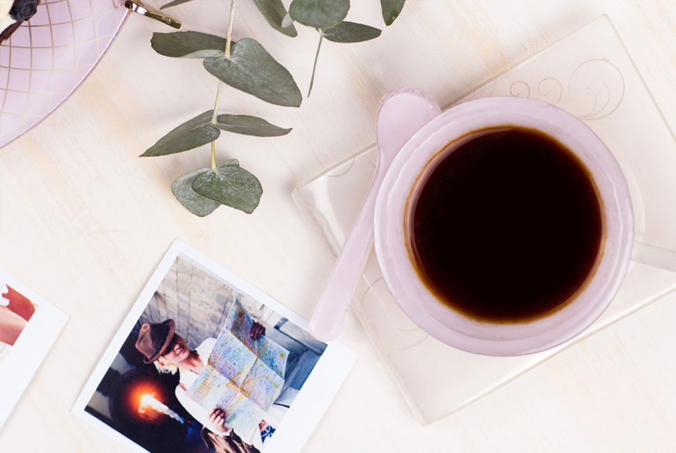 Top view of pink glass coffee cup Urse with coffee and a polaroid picture