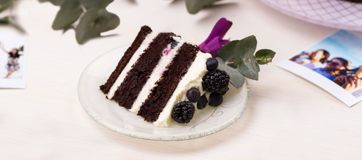 Chocolate cake with white frosting on a beige glass dessert plate with a floral pattern.