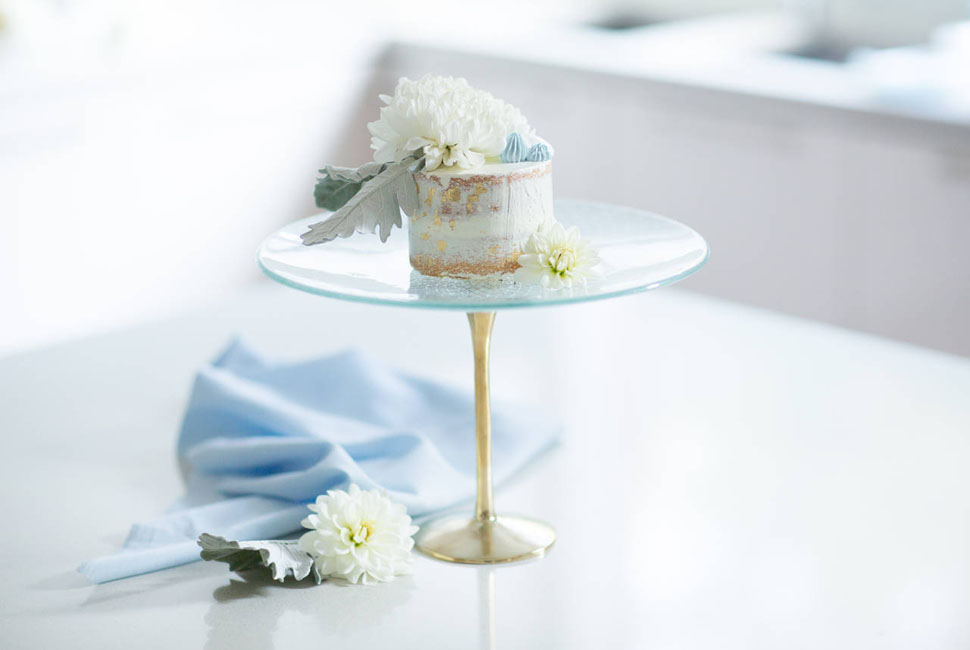Small blue Glass Cake Holder with a bronze pedestal and a retro pattern by Anna Vasily for Baking Day with a small rustic cake on a white kitchen table.