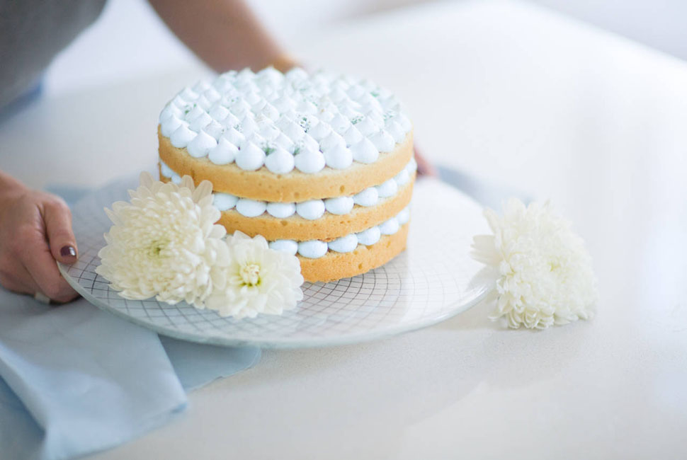 Stylish white glass cake holder with a geometric pattern by Anna Vasily with a naked cake being set down on a white table by a woman's hands.