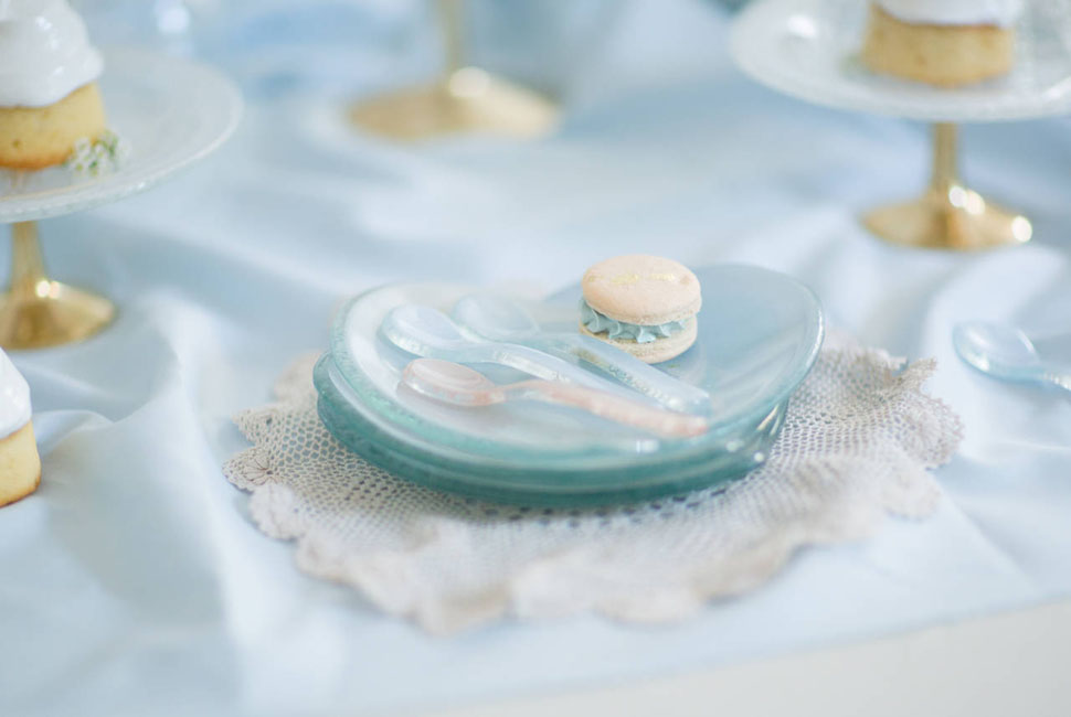 heart shaped glass plate in light blue with little glass spoons and a french macaroon on top