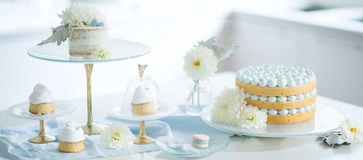 Stylish Blue Glass Cake Holders with Bronze Pedestal and Retro Patterns by Anna Vasily for Baking Day with Different Cakes on a White Kitchen Table