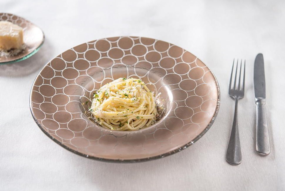 Brown pasta plate with a wide rim and a geometric pattern with a serving of pasta and a knife and fork.
