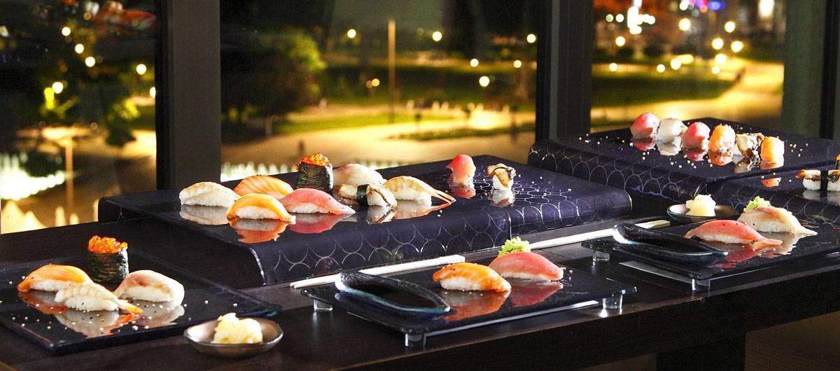 Elegant navy blue Japanese sushi sets by AnnaVasily with a night time city street seen through the windows behind them