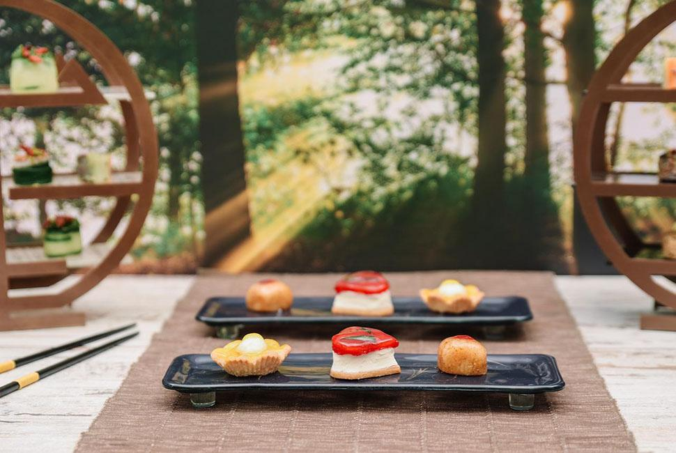 2 glass tea trays Blos with appetisers and chopsticks between 2 round high tea stands with a sunny forest in the background.