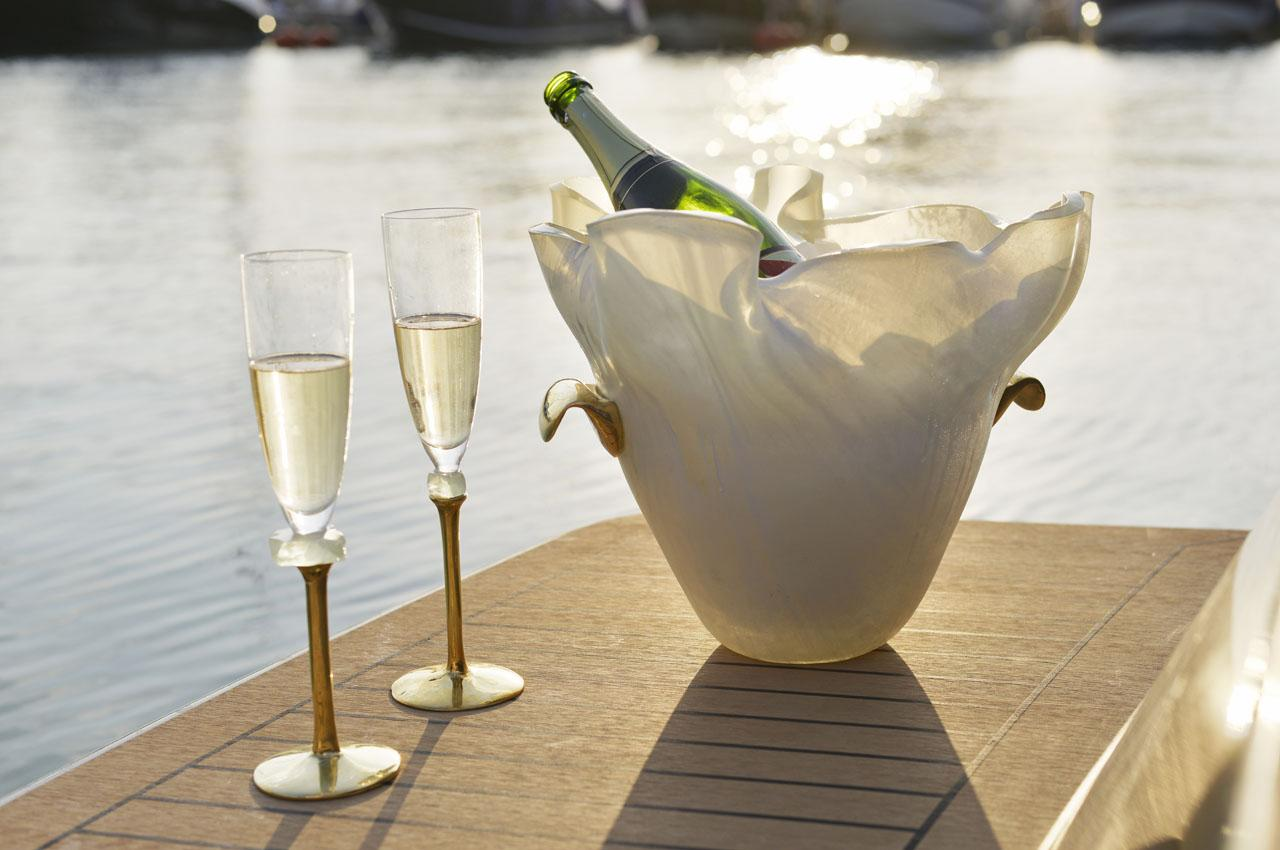 Elegant champagne bucket with bronze handles and a bottle of champagne with 2 champagne glasses from a blue dinner set.