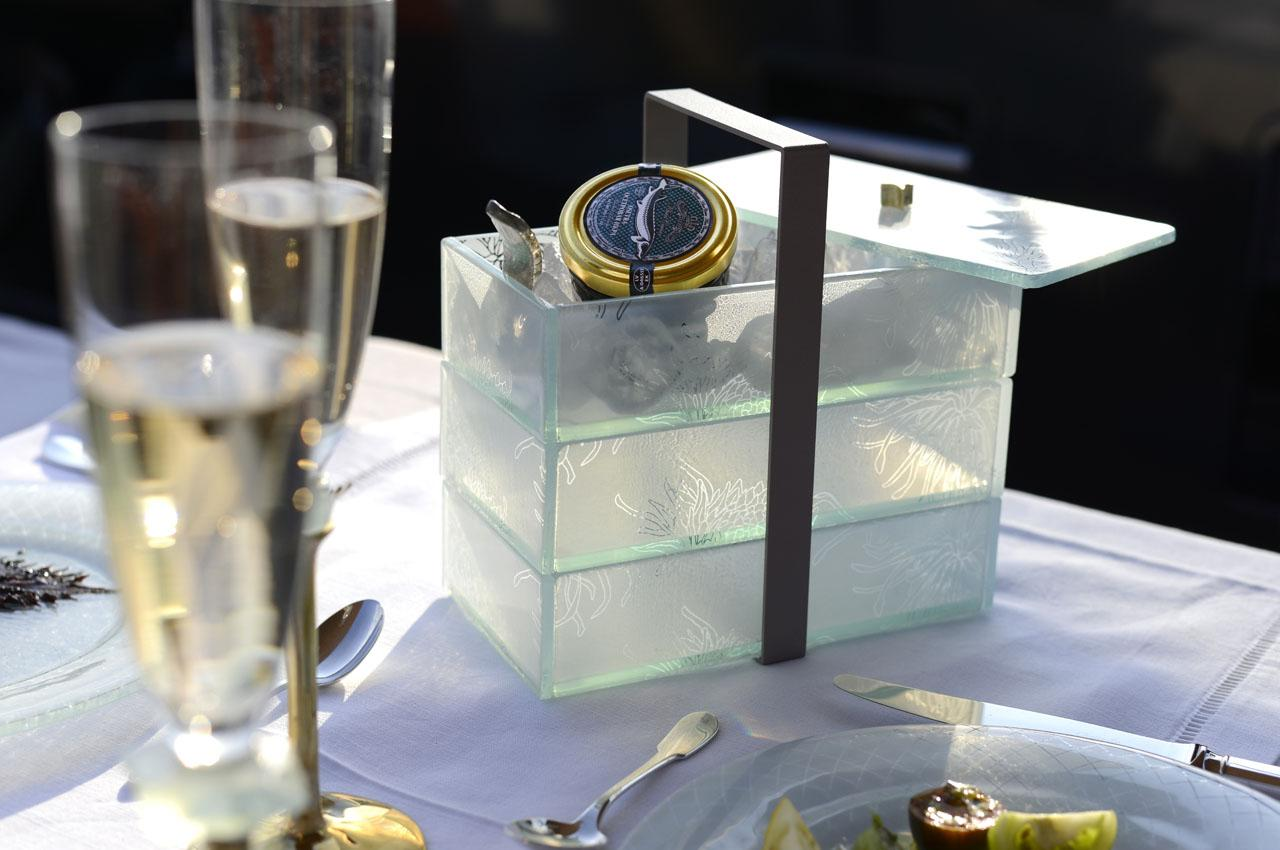 Sailboat table setting with a blue dinner set and a glass jewelry box made to look like a bento box with a fancy watch.