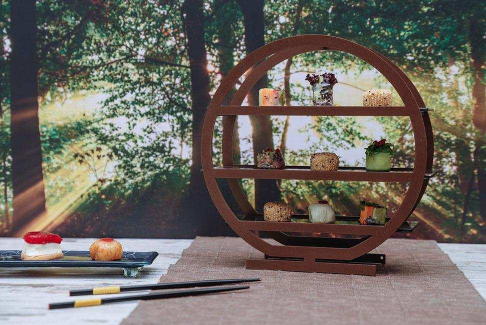 Tea tray Nata is a round tiered high tea stand with three tiers. Nata stands on a sunny forest background and is presenting beautiful Japanese desserts.