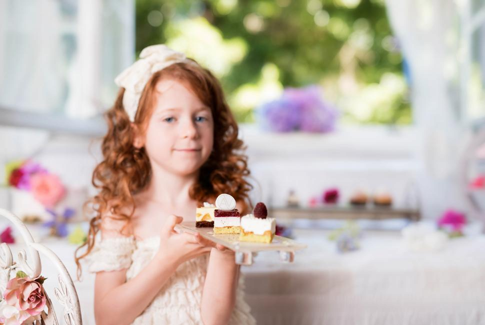 Redheaded little girl dressed in white holding a rectangular petit fours plate with 3 petit fours.