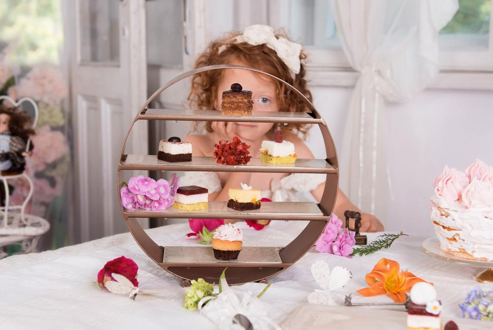 Redheaded little girl behind the round Afternoon Tea Stand Deu by AnnaVasily with small desserts for a High Tea doll party.
