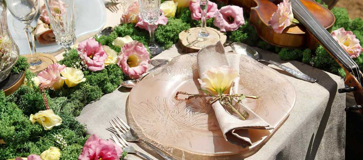 A floral tablescape with moss and a pink floral decorative plate with a folded napkin.