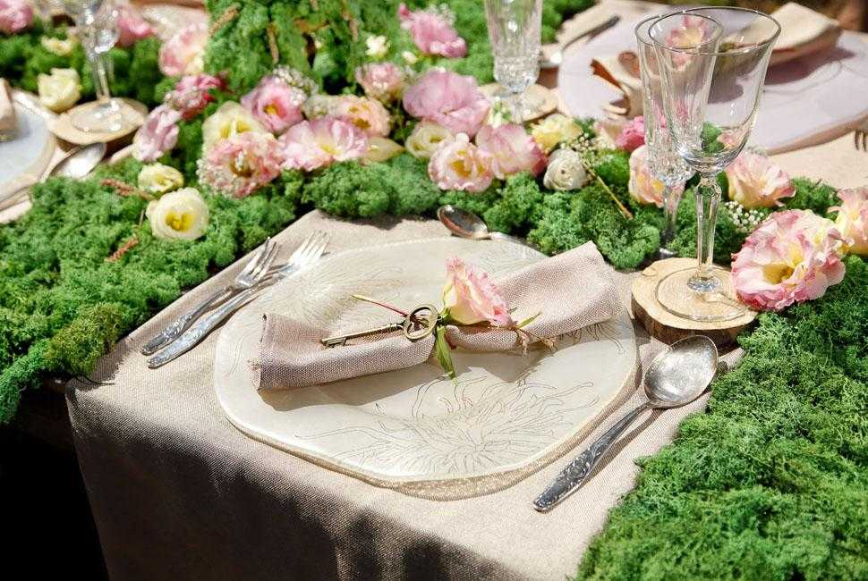 A place setting with a floral decorative plate surrounded by moss and flowers.