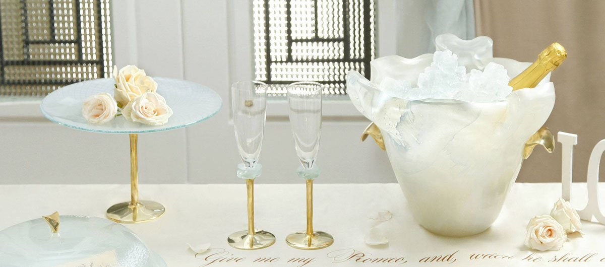 Elegant and romantic table setting including champane bucket, glass dome, champagne glass, cake stand a small glass bowl with a lot of flowers and a Sheakspeare sonnet written on the table cloth