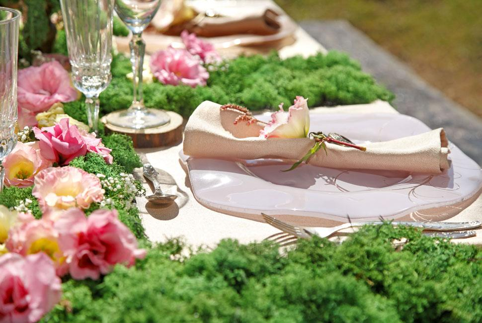 Spring table with moss and flowers with a pink floral decorative plate.