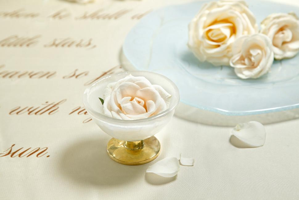 Romantic beige ice cream bowl on a pedestal with a white rose in it, on a table with a poem and a light blue charger plate.