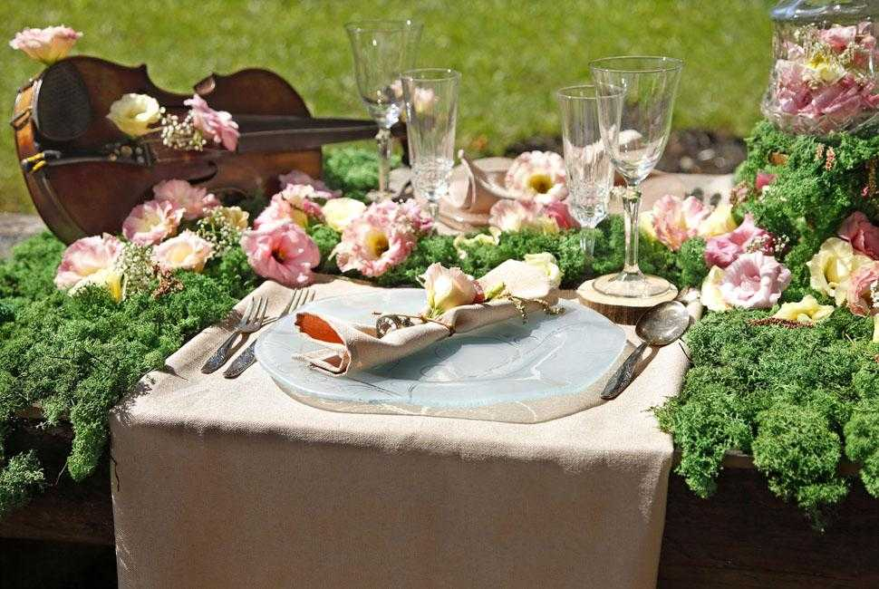 Place setting with a large blue decorative floral plate, surrounded by lots of moss and flowers.