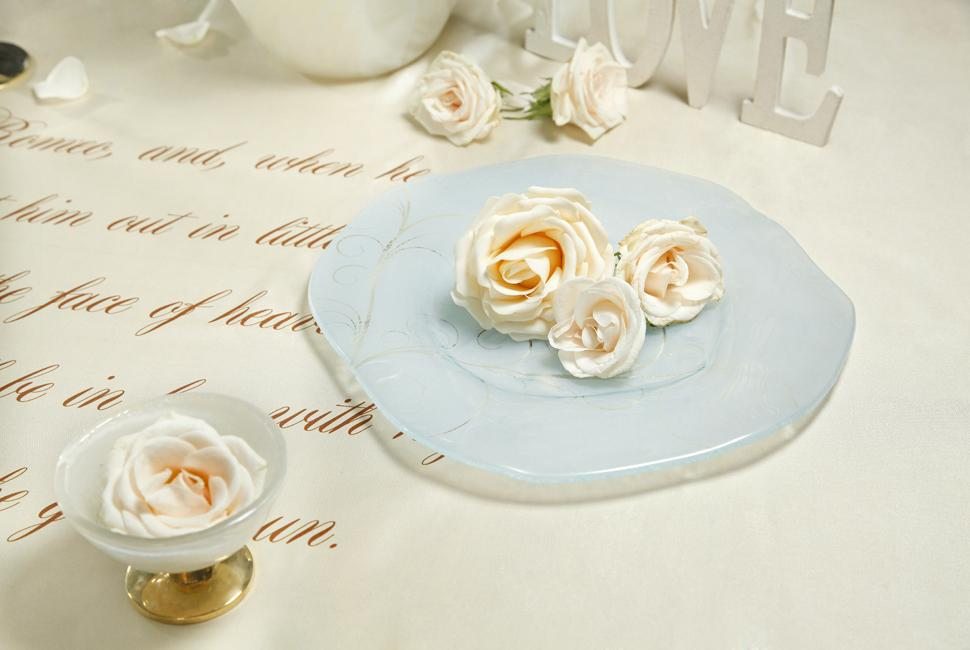 An irregular shaped blue charger plate with white roses on a table with a sonnet on the tablecloth.
