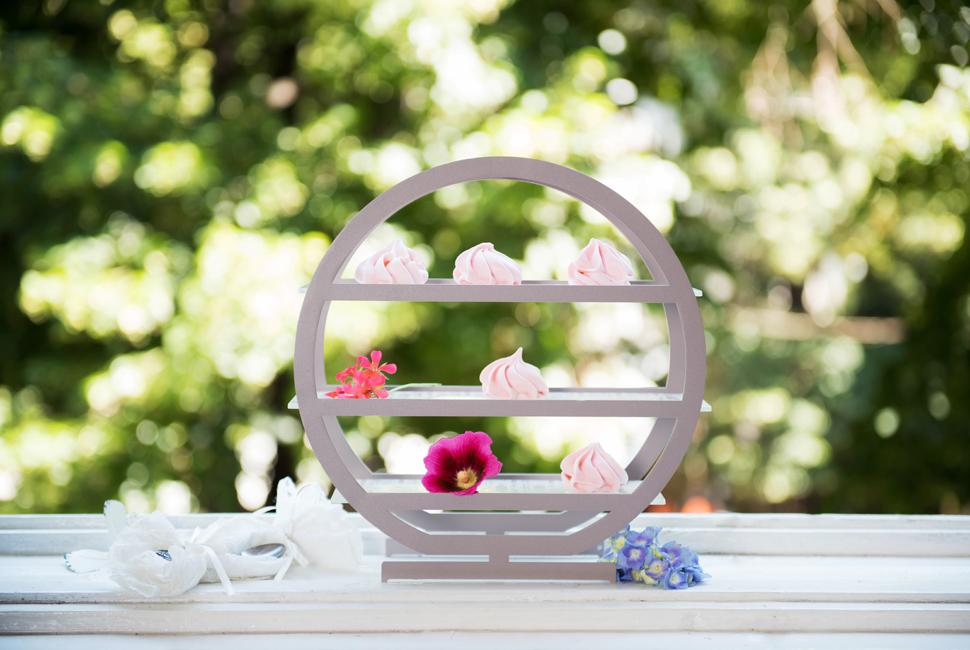 Round Afternoon Tea stand Olim by AnnaVasily with pink meringue kisses on a white windowsill with trea leaves seen outside.