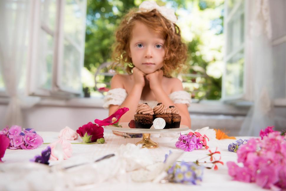 Redheaded little girl behind a table with an Afternoon Tea display with flowers and small gold cake stand with a pedestal with chocolate cake.