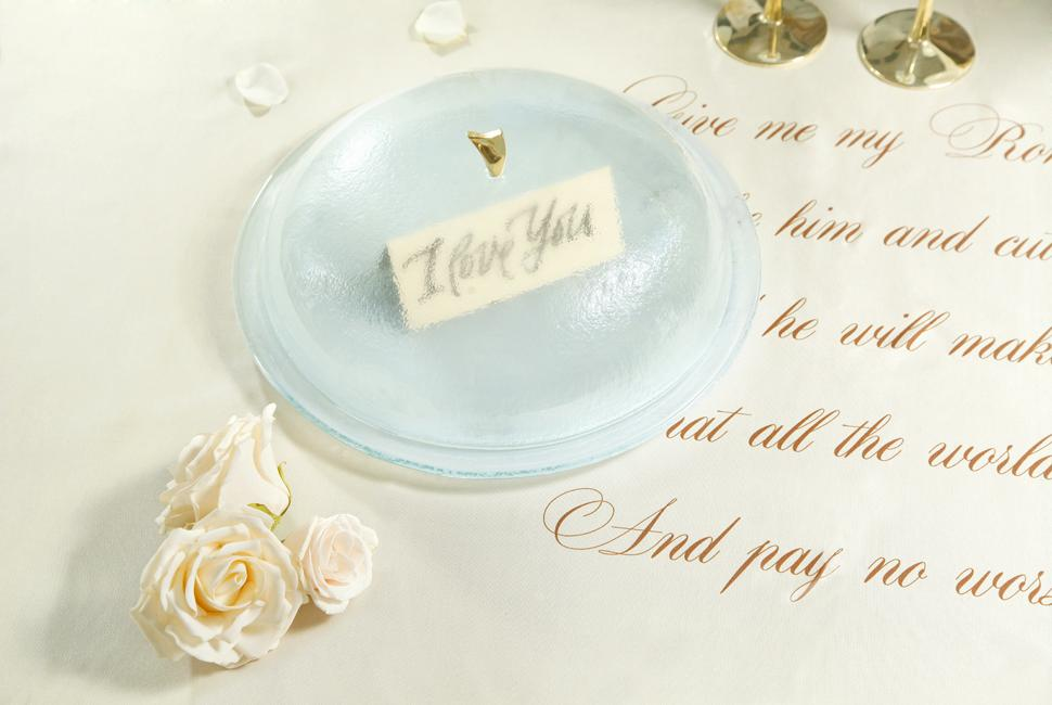 Light blue serving platter with a glass dome with a love note under it on a table with a poem and roses