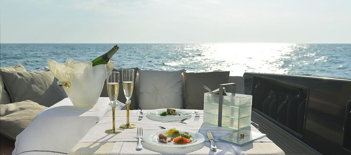 A sailboat tablescape with a blue dinner set, a beige blue champagne bucket, 2 champagne glasses and a light blue jewelry box.