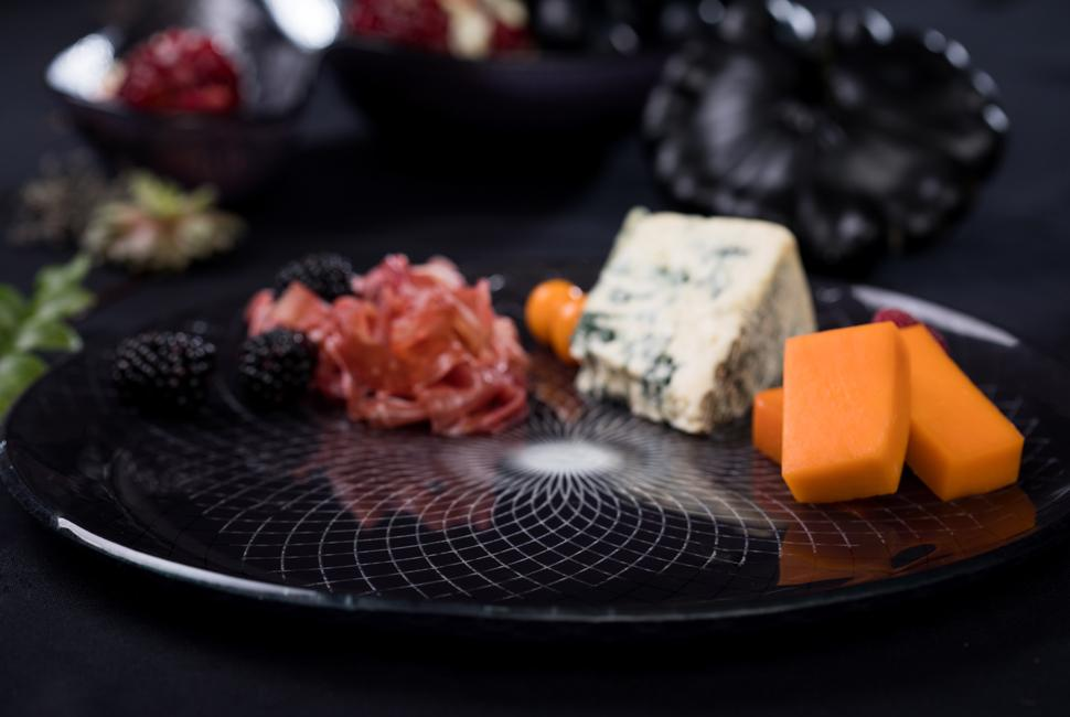 Kate is a big round dinner plate with a gently raised rim, in magical deep night blue with our lattice Venetian Filigree pattern. On the image Kate is presenting as a finger food platter cheese and meat bites as part of an environment of a Halloween tablesetting.