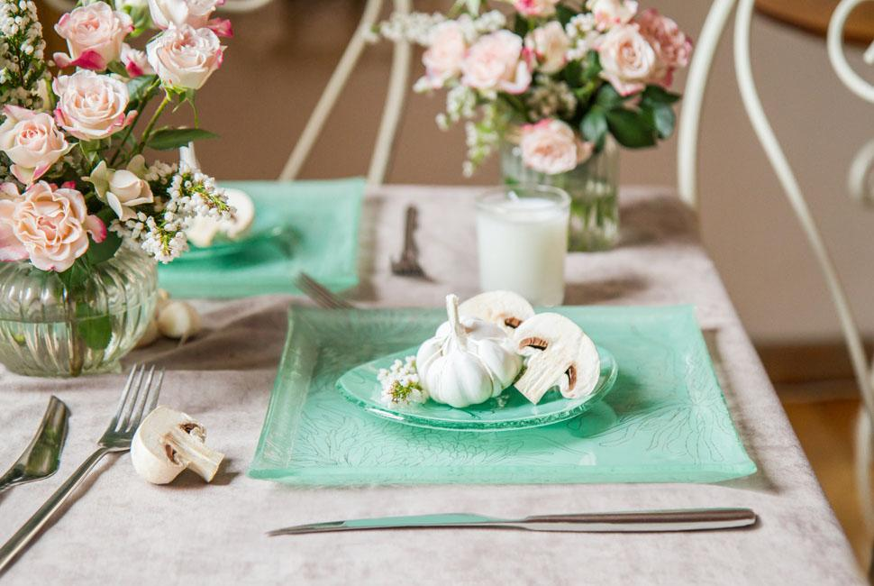 Square Plate Beautiful elegant mint green table setting with white raw vegetables on top. Rustic garlic and mushrooms with creme flowers arrangements.