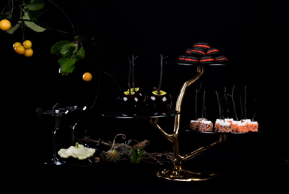 High tea stand in the shape of a tree branch used as Halloween table decorations with halloween treats on a dark and moody table.