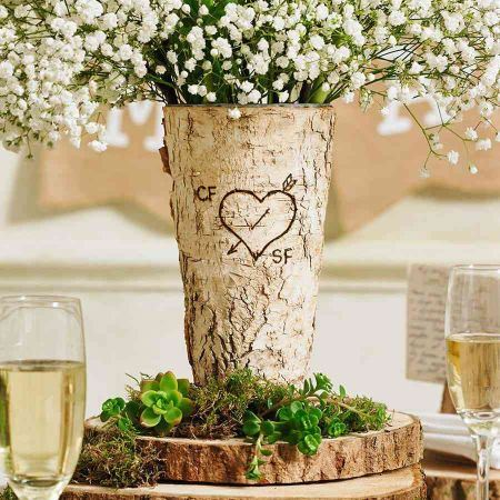 Fairy like environment table setting with a vase made from real tree and a heart carved on it with white flowers. On the table are also glasses of wine