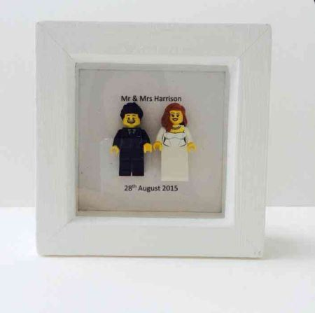 Picture frame with 2 small lego figures refering to the new couple