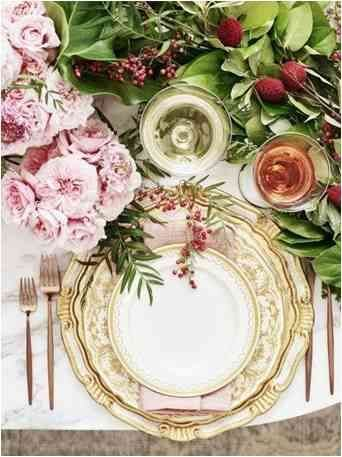 well set table with floral dinnerware with golden cutlery, fresh flowers and wine glasses