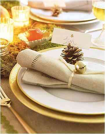 silver bell used as napkin holder in a christmas setting