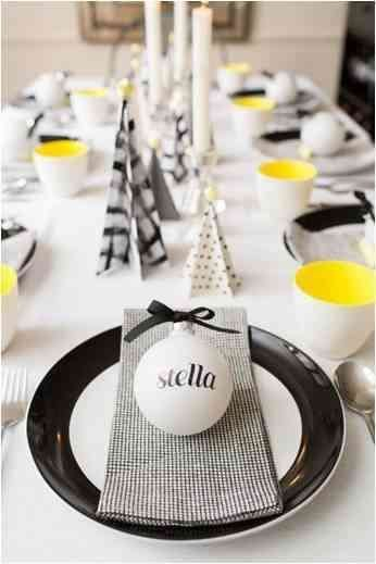 Christmas table setting in minimalistic white and black with yellow elements with customized Christmas toy in white with black ribbon