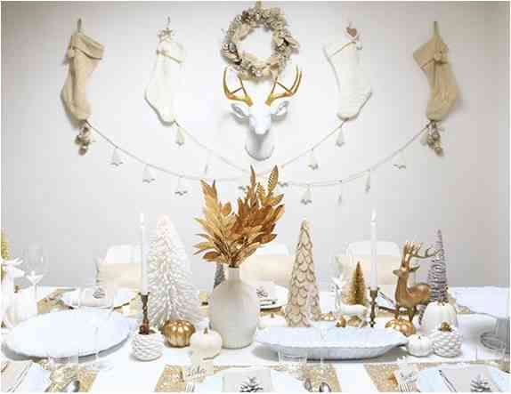 White Christmas table with stockings on the wall for authentic style. Earhly colours and leaves in the center table setting