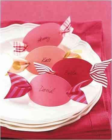 Colourful place cards in red and pink and the shape of bonbons