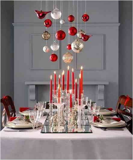 Christmas table setting in red and white with hanging from the top decorations