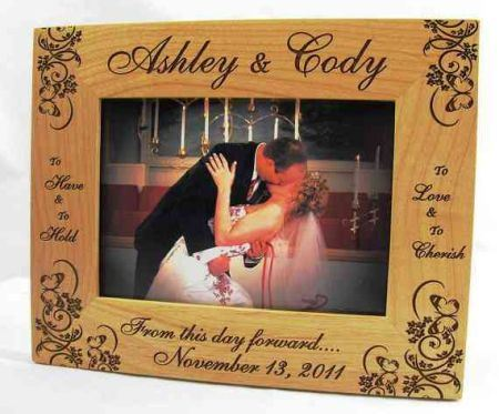 Customized wooden picture frame with the names of Ashley and Cody and their wedding details. In the frame is a picture of the couple kissing on their wedding day.