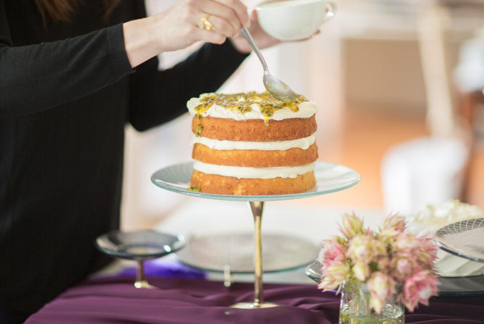 Woman decorating a naked cake on a light blue glass cake stand with a bronze pedestal.